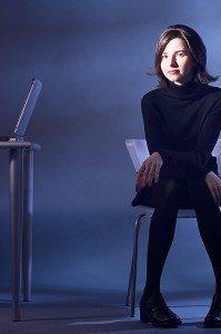 Woman in black dress sitting 4 feet away from laptop