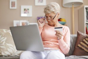 Senior with glasses making an on-line purchase by credit card