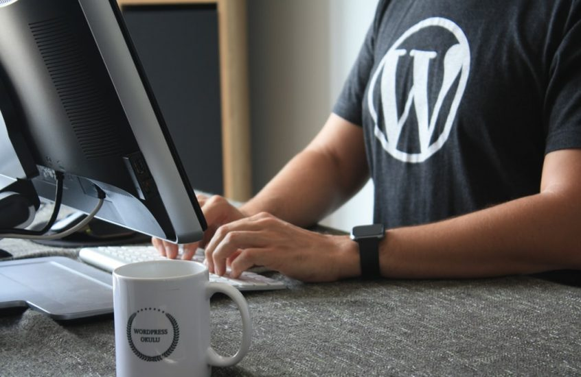 developer at computer with WordPress icon on t-shirt