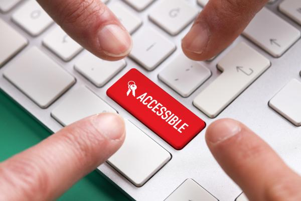 Red keyboard key with word Accessible, with 4 fingers reaching for it